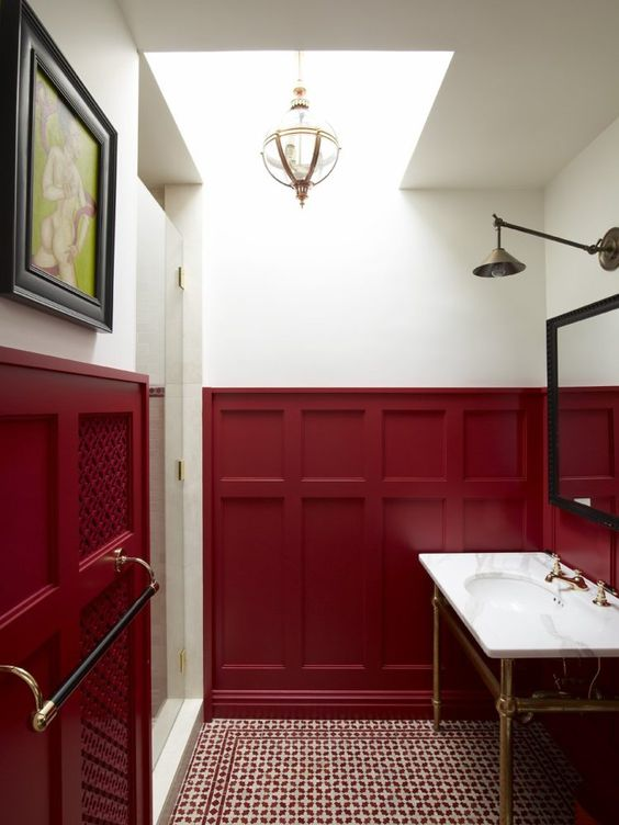 a refined powder room with burgundy wainscoting, a white sink, a large mirror, pendant and wall lamps