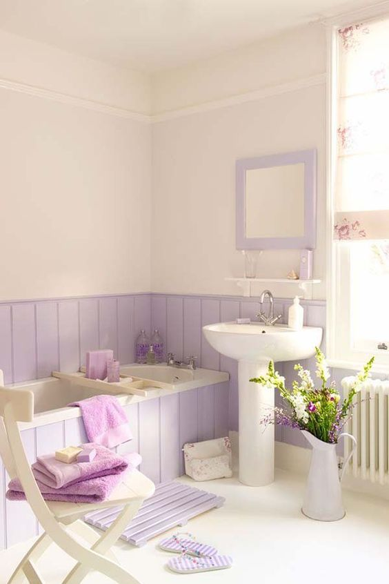 a romantic bathroom with lavender paneling and a mirror, a wooden mat and a vase plus purple towels