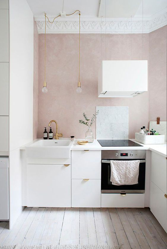a small and serene contemporary kitchen with blush walls, white cabinets with gold pulls, pendant bulbs and a white hood