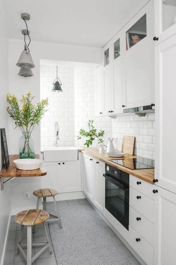 a small contemporary kitchen in white with walls done with tiles, a folding mini table, metal and wood stools and pendant lamps