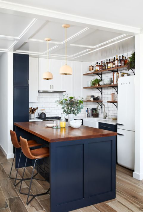a small farmhouse kitchen in white and navy, with a kitchen island with a stained countertop, pendant lamps and a subway tile backsplash