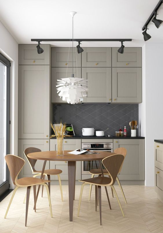a small grey kitchen with a farmhouse feel, black lamps, a plywood dining set for a laconic and simple look