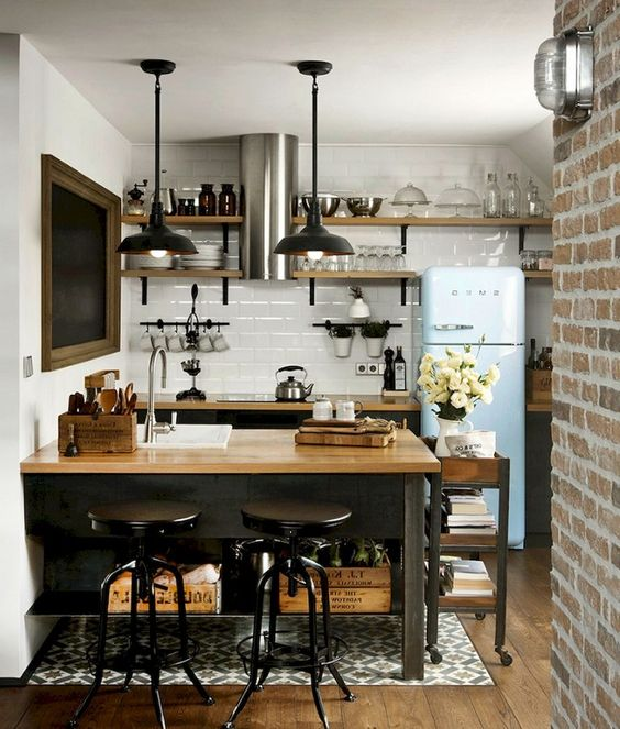 a small industrial kitchen with blackcabinets and a kitchen island plus butcherblock countertops, black pendant lamps and a blue fridge