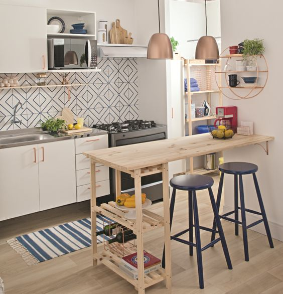 a small light-filled kitchen with a mosaic tile backsplash, a pallet kitchen island with a meal space, white cabinets and touches of copper