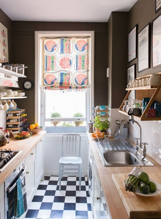 a small monochromatic kitchen with black walls, a white subway tile backsplash, butcherblock countertops and a colorful shade