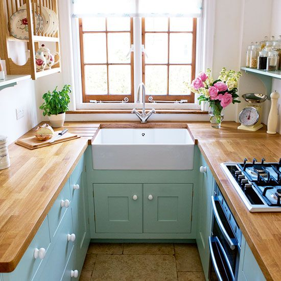 a small pastel farmhouse kitchen with mint cabients, butcherblock countertops, wooden open shelves and a window with wooden framing