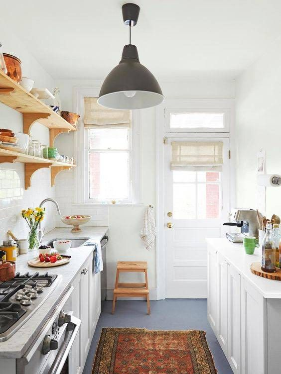 a small rustic kitchen with white cabients, open shelves, a printed rug, a pendant lamp and windows for natural light