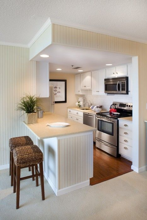 a small traditional kitchen in off-white placed into a cube, with a kitchen island that separates the spaces