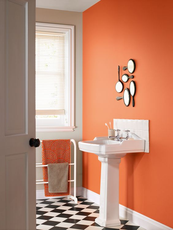 a statement rust wall with a arrangement of hand mirrors and a matching towel to spruce up a monochromatic bathroom