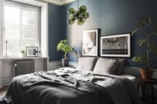 a stylish and relaxing bedroom done in greys and with a navy statement wall, with greenery and green accents
