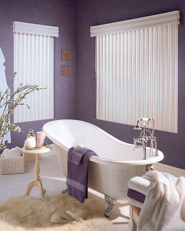 a stylish bathroom with purple walls and towels, an elegant vintage bathtub, side tables and a wicker box