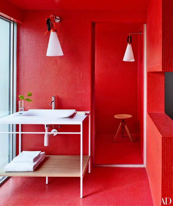 a super bright red bathroom with white appliances and furniture, with white lamps for a bold look