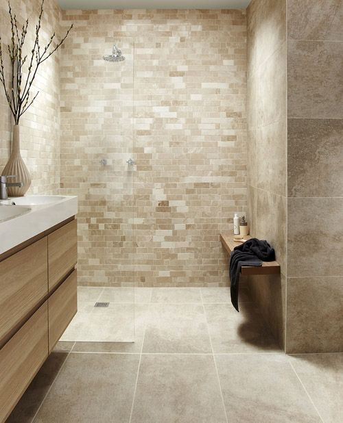 a tan and taupe bathroom clad with tiles of various sizes, a beige vanity and white sinks