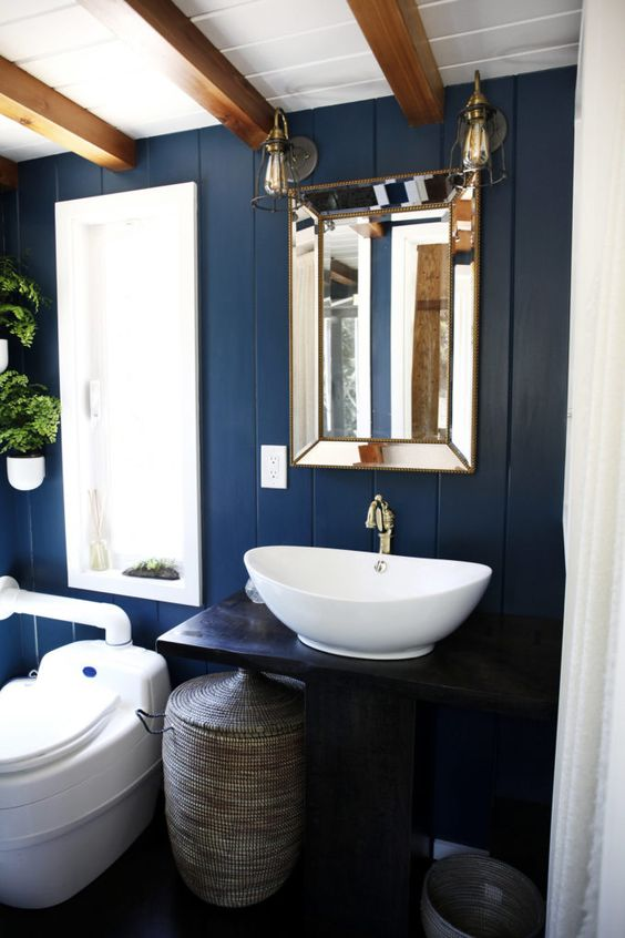 a tiny bathroom done with blue painted wood, wooden beams on the ceiling and a basket for storage