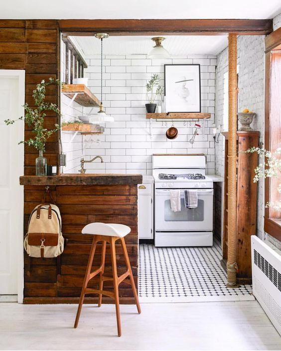 a tiny kitchen done in white and with rich-stained wooden surfaces, potted greenery and a mosaic tile floor