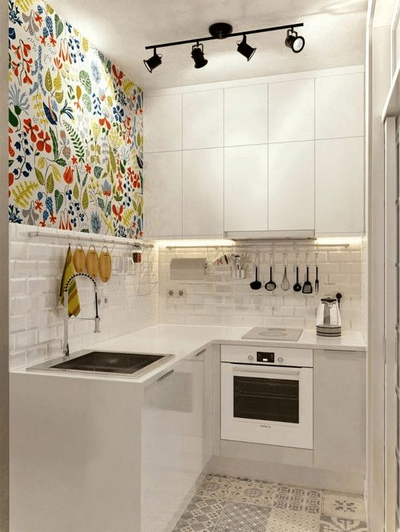 a tiny minimalist kitchen with sleek white cabinets, a colorful wall, a white tile backsplash and a mosaic tile floor