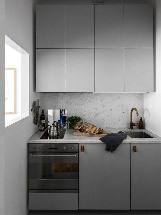 a tiny minimalist kitchen with sleke grey cabinets, leather pulls and a grey stone backsplash