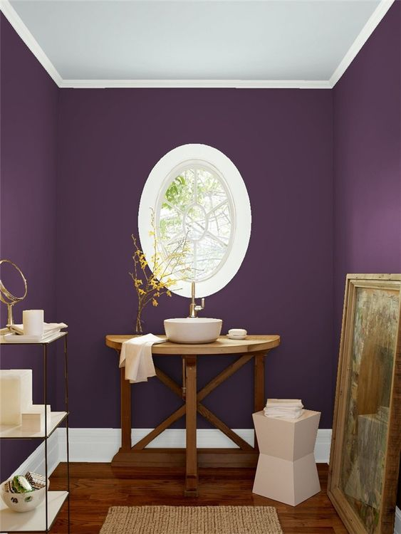 a unique purple bathroom with an oval framed window, a wooden vanity and a vessel sink, an etagere and an artwork