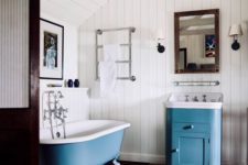 a vanity and a clawfoot bathtub done in blue add a touch of chic color and make the space catchy