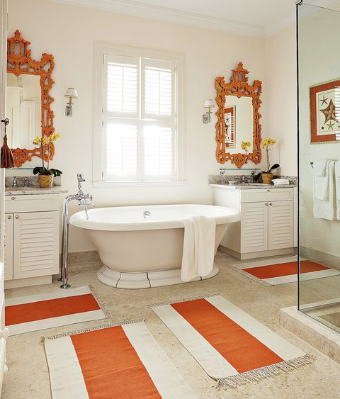 a vintage-inspired bathroom done in neutrals and accented with orange ornate mirrors and striped rugs