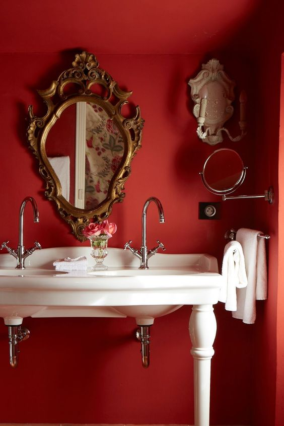 a vintage red powder room with red walls, an antique white vanity with sinks and exquisite mirrors