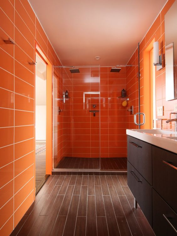 a warm bathroom with orange tile walls and wood-inspired tiles on the floor for a bright and welcoming space