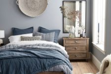 a welcoming light grey bedroom with wooden furniture and blue bedding