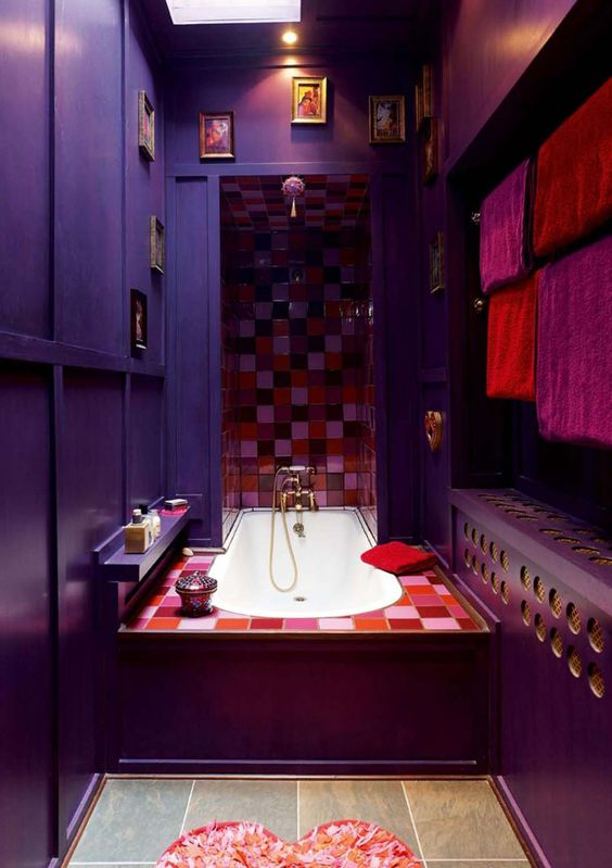 a whimsical Moroccan-inspired bathroom with purple and aubergine walls, bright mosaic tiles, a gallery wall and a heart-shaped rug