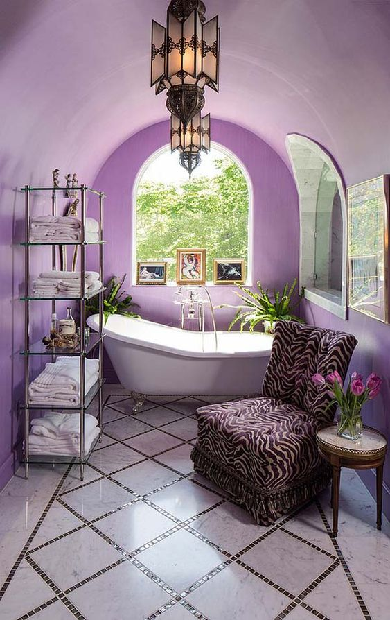 a whimsy lavender bathroom with a Mediterranean feel, unique pendant lamps, a zebra print chair and a catchy glass etagere
