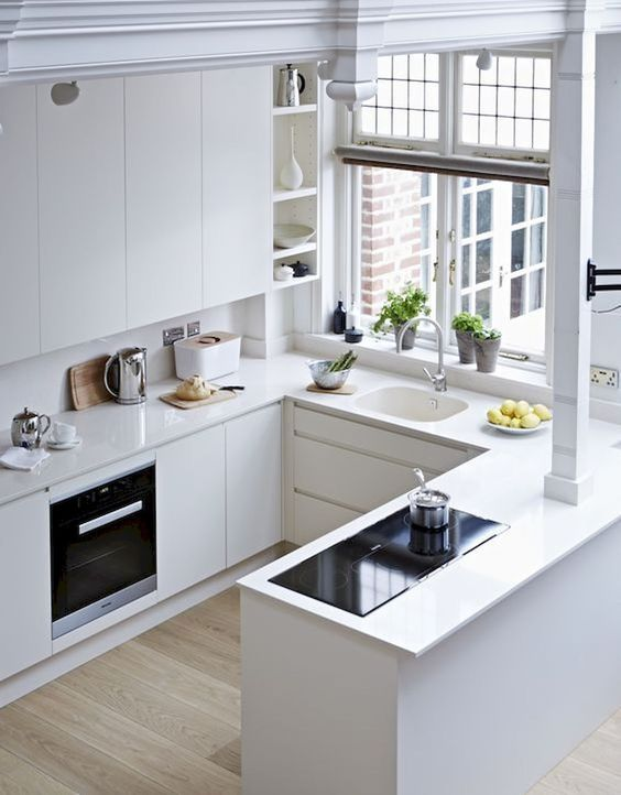 a white minimalist kitchen with sleek cabinets, no handles, a window and simple built-in appliances