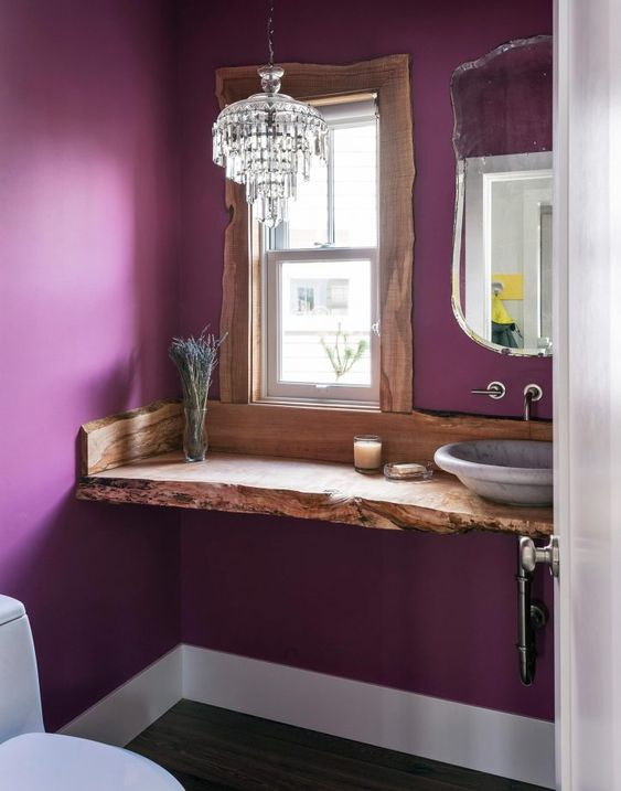 an eclectic bathroom with purple walls, a wooden vanity with a livign edge, a crystal chandelier and a lavender vessel sink