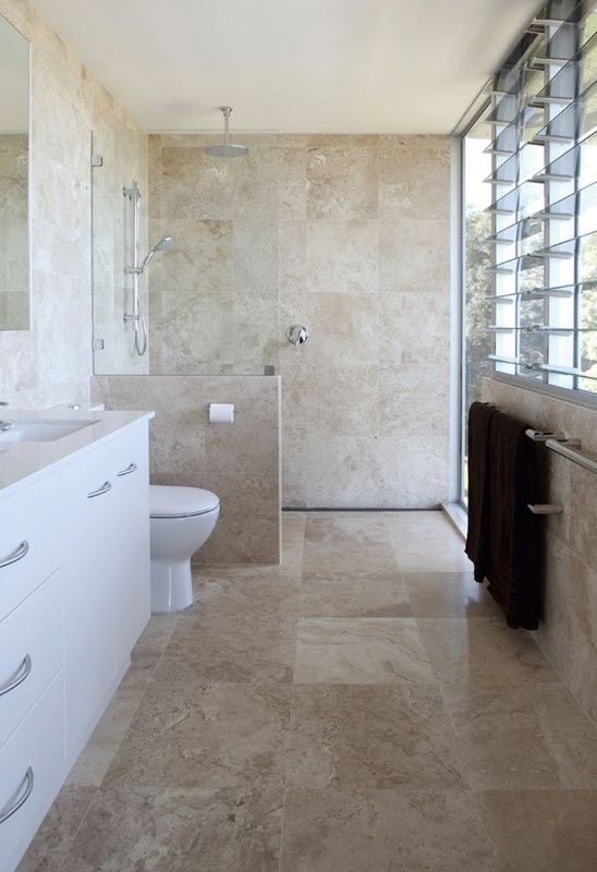 beige stone-inspired tiles covering the whole bathroom, white items and a vanity for an elegant look