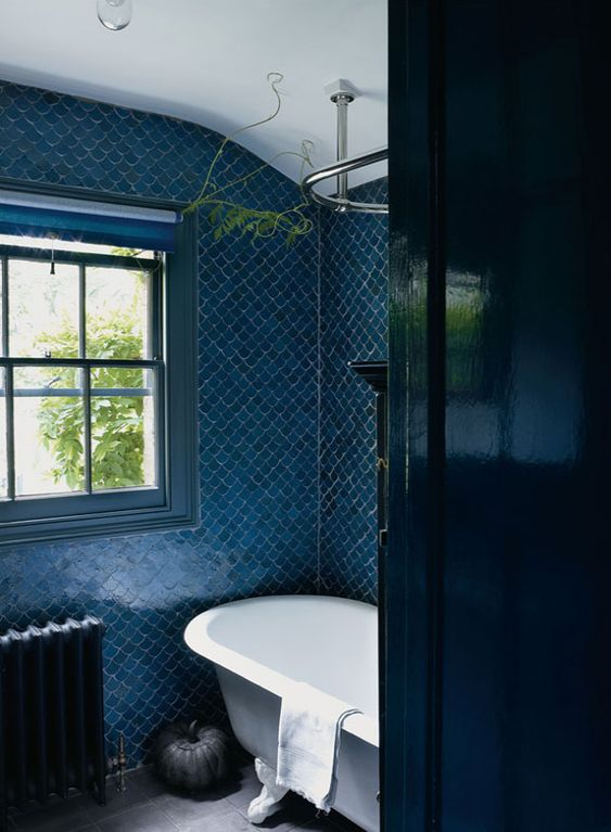 blue fish scale tiles, a navy door, a navy radiator and a blue window frame create a vibrant space