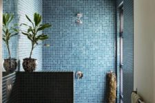 bold blue mosaic tiles in the shower, a half wall, greenery and a vessel sink plus a window for the view
