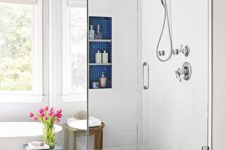 bright blue tile touches – shower floors, a niche for storage and an elegant side table