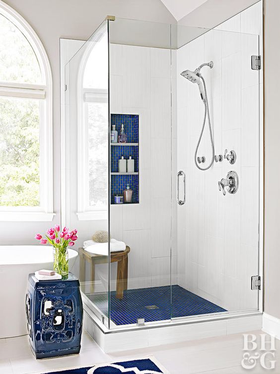 bright blue tile touches - shower floors, a niche for storage and an elegant side table