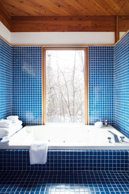 bright blue tiles with white grout all over the bathroom plus light-colored wooden frames and ceilings