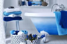 bright blue touches – a rug, towels, fabric baskets and a bright ombre blue clawfoot bathtub for a chic space
