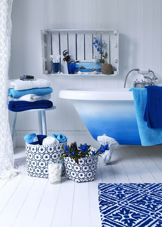 bright blue touches - a rug, towels, fabric baskets and a bright ombre blue clawfoot bathtub for a chic space