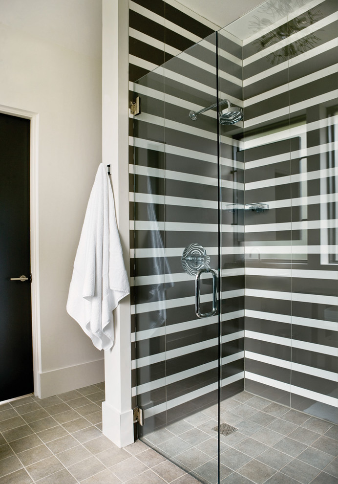 corner shower with horizontal monochrome stripes is difinitely a focal point of this space