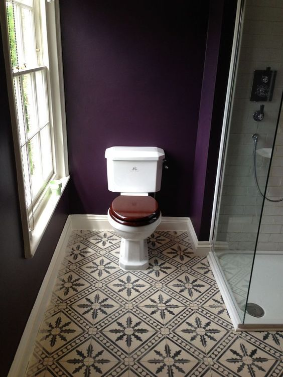 deep purple walls and mosaic tiles on the floor make this bathroom elegant, chic and very decadent