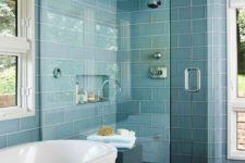 light blue subway tiles with white grout, dark wooden floors and a white bathtub are a cool setup for a modern bathroom