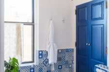 mismatching blue mosaic tiles and a bright blue door with white touches make up a chic and inspiring bathroom