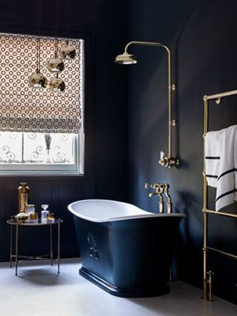 navy painted bathroom walls, a navy bathtub, pritned Roman shades, pendant lamps and a side table