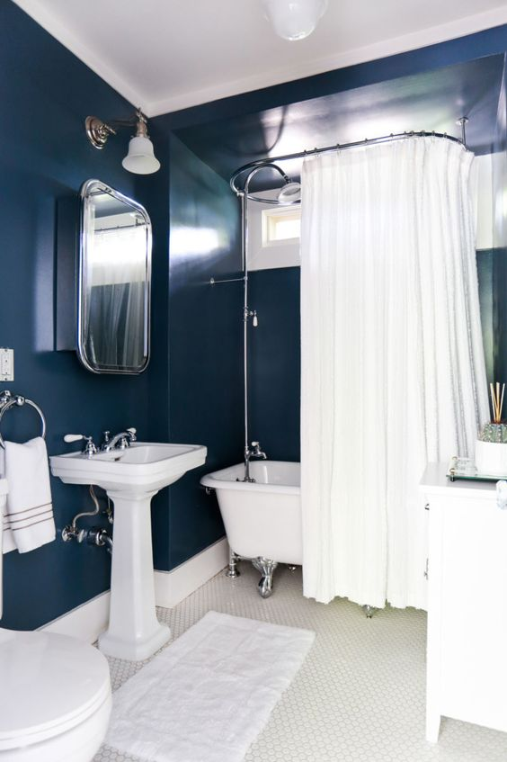 navy painted walls paired with all the rest in creamy shades is a chic idea to create a bold bathing space
