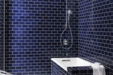 navy subway tiles with white grout and a bathtub clad with the same tiles is a chic and bold contemporary idea
