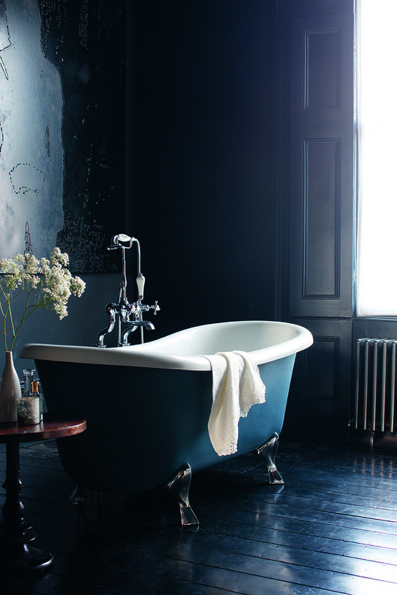 navy walls and a navy wooden floor, a navy clawfoot bathtub, a side table plus shutters show off refined vintage