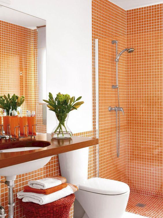 orange tiles on the walls and in the shower can be accented with white grout and orange towels to match