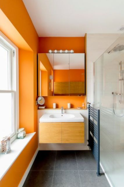 orange walls paired with grey tile floors and all white everything create a fresh and bright summery look in your bathroom