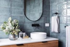 slate blue grey tiles, a wooden floating vanity, an oval mirror and a round sink plus a tree stump stool